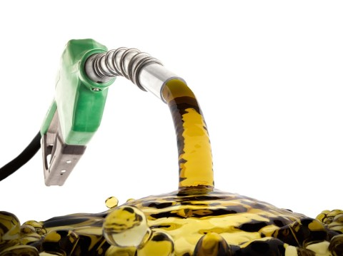 Green gas nozzle wasting fuel on white background